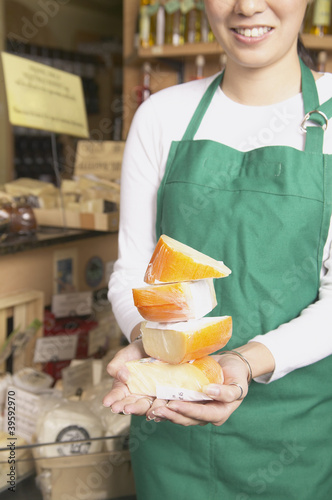 Asian female supermarket worker with cheese