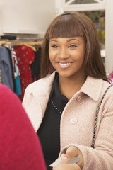 African American woman making credit card purchase at boutique