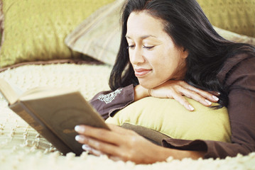 Woman reading book on bed