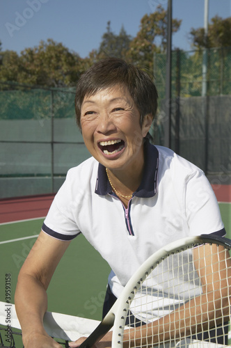 Senior Asian woman laughing on tennis court
