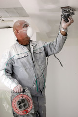 Man sanding a plasterboard ceiling