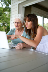 a grandmother and her granddaughter doing computer