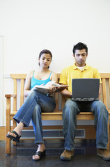 Woman reading and man using laptop