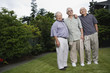 Portrait of three elderly men standing in yard