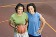 Portrait of two teenage girls with basketball on court