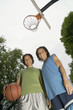 Low angle portrait of two teenage girls with basketball on court