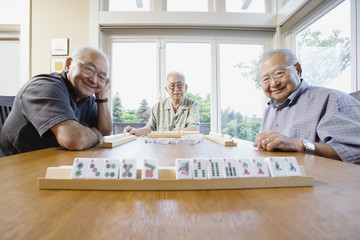 Portrait of three elderly men sitting at table playing game