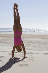 Portrait of girl doing handstand on beach