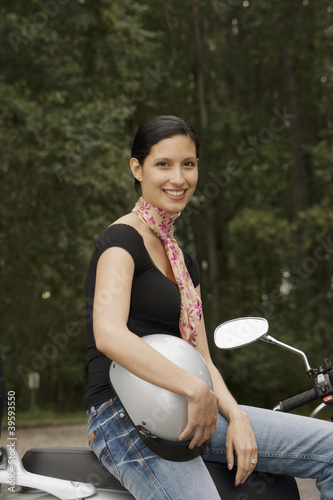 Portrait of woman on scooter holding helmet