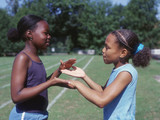 Two girls playing clapping game