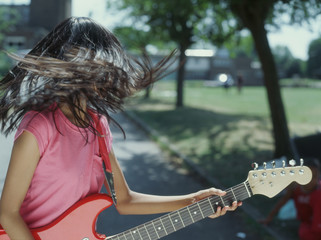 Teenager tossing hair while playing guitar