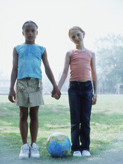Full view portrait of two girls holding hands