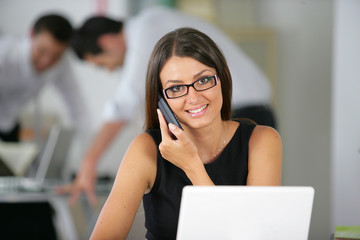 Friendly office worker with a phone and laptop
