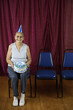 Seated woman with party hat and birthday cake