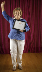 Woman holding certificate triumphantly