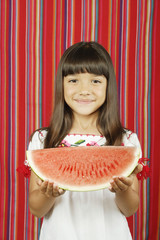 Young girl holding slice of watermelon