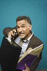 Portrait of man with briefcase and files talking on cell phone