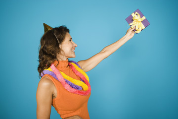 Side view of woman holding up gift birthday hat