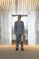 Young businessman standing outside of elevator