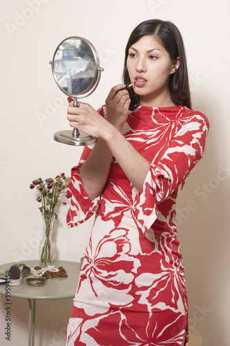 Woman holding mirror and applying lipstick