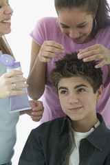 Two teenage girls styling teenage boy's hair