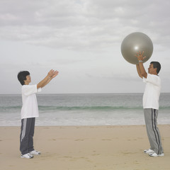 Couple playing with ball at beach