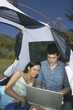 Couple in tent with laptop