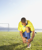 Soccer player tying shoe