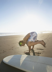 Man exercising in sand with surf board