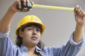 Woman construction worker with measuring tape and hard hat