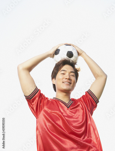 Portrait of soccer player holding ball on top of head