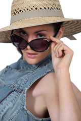 Woman wearing straw hat and sunglasses