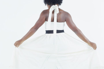 Rear view of woman fanning out skirt of white dress