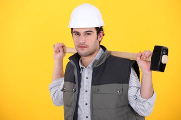 A man carrying a sledgehammer.