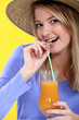 Girl in straw hat drinking orange juice through straw
