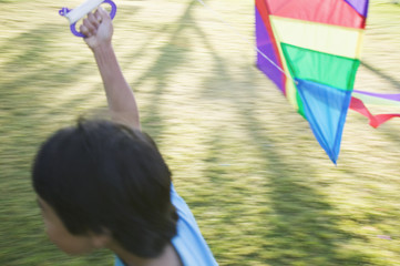 Blurred image of boy flying kite