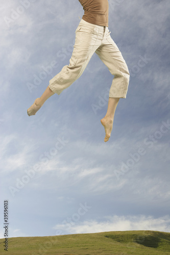 Lower section of woman jumping in air