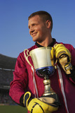 Male goalie triumphantly holding trophy