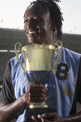 Male soccer player proudly holding trophy