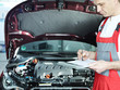 Motor mechanic in front of engine bay is checking repair details