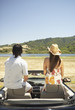 Couple sitting on headrests inside a convertible
