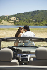 Couple kissing outdoors with convertible in foreground