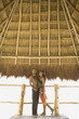 Couple standing underneath thatch roof