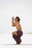 Young man practicing yoga on the beach