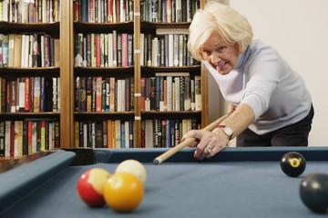 Elderly woman shooting pool