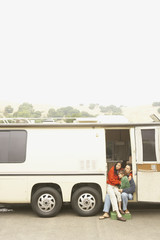 Mother and son sitting in doorway to recreational vehicle