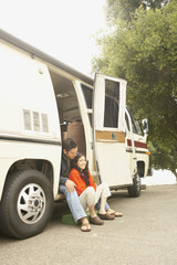 Couple sitting in doorway to recreational vehicle