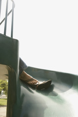 Woman's sandaled feet resting on children's slide