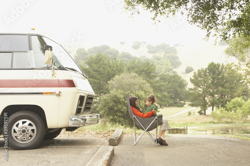 Mother and daughter sitting by truck outdoors