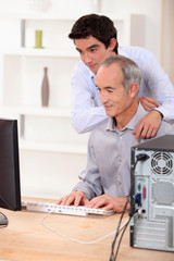 A father and a son looking at a computer screen.